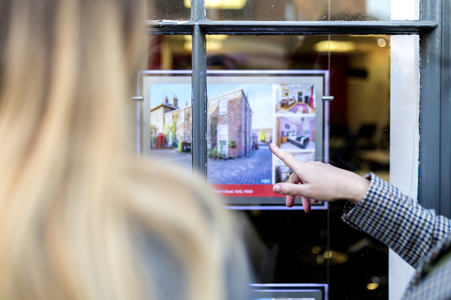 Couple Looking And Pointing At A Property Advert In The Window O